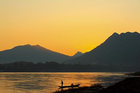 Laos fisherman at river  on sunset